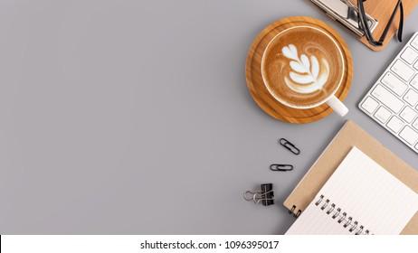 Flachbildschirm, Schreibtisch mit Draufsicht. WorkSpace mit leerem Notenbuch, Tastatur, Bürobedarf und Kaffeebecher auf grauem Hintergrund.
