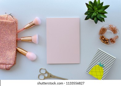Flat lay, top view office table desk workspace with office and beauty with brushes, blank paper and plant on white background.