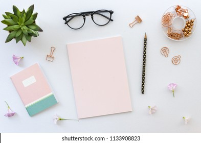 Flat lay, top view office table desk workspace with office accessories including blank paper for lettering, notepad, glasses and plant on white background. mockup