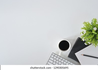 Flat lay top view office desk. Workspace with keyboard and office supplies with coffee on white background.