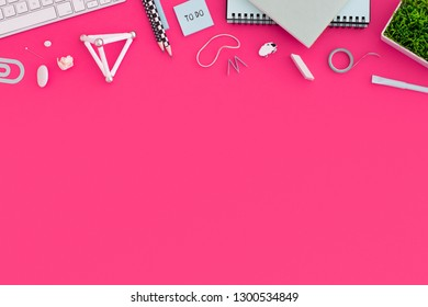 Flat lay, top view office table desk. Workspace with spiral notebook, keyboard, office supplies, pencil, green plant on pink background.