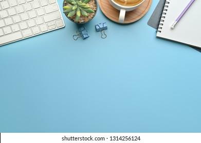 Flachbildschirm, Schreibtisch mit Draufsicht. WorkSpace mit leerer Bespannung, Tastatur, Bürobedarf, Bleistift, grünem Blatt und Kaffeetasse auf blauem Hintergrund