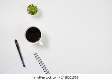 Flat lay, top view office table desk. Workspace with blank notepad, office supplies, green leaf, and coffee cup on white background.