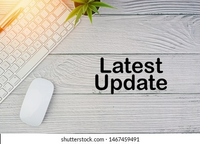 Flat lay, top view office table desk. Workspace with LATEST UPDATE inscription written with keyboard, mouse and pen on wooden background. Business, Insurance and Islamic concept