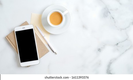 Flat lay, top view office table desk. Freelancer workplace with cup of coffee, paper notebook, office supplies and smartphone screen mockup