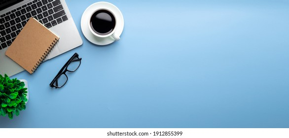 Flat lay, top view office table desk. Workspace with, laptop,office supplies, pencil, green leaf, and coffee cup on blue background.
