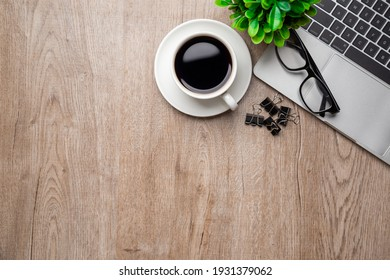 Flat lay, top view office table desk. Workspace with, laptop,office supplies, pencil, green leaf, and coffee cup on wood background.