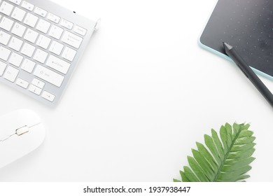 Flat lay, top view office desk. Office supplies, keyboard, mouse, pen mouse, and tropical leaf on white office desk background with copy space, workspace blank. Office desk concept.