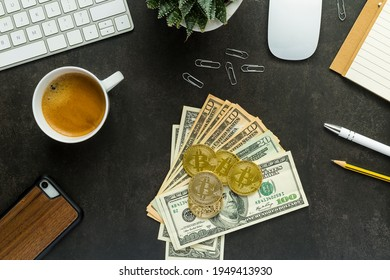 Flat lay top view office desk working space with keyboard and smartphone, watch, plant, coffee, usd dollars and bitcoin on black background