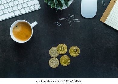 Flat lay top view office desk working space with keyboard and smartphone, watch, plant, coffee, bitcoins coins on black background