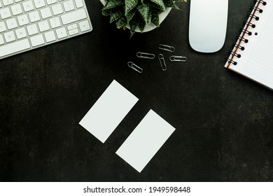 Flat lay top view office desk working space with keyboard and smartphone, watch, plant on black background, blank business card