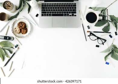 Flat lay, top view office table desk. Workspace with laptop, glasses, cup of black coffee, cookies on golden tray, pencils, paintbrushes and leaf.