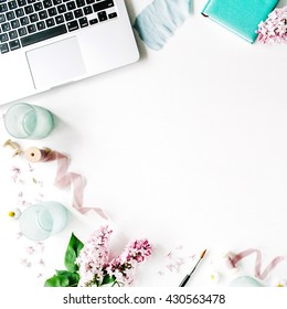 Flat lay, top view office table desk. laptop, lilac flowers bouquet, spool with beige and blue ribbon, mint diary on white background.