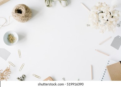 Flat lay, top view office table desk. feminine desk workspace frame with twine, pencils, floral bouquet, craft diary and clips on white background.