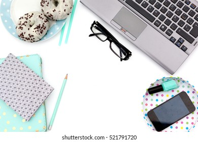 Flat lay, top view office table desk frame. Workspace with laptop,donuts, mint diary, glasses mug and nail polish, mobile device on white background
