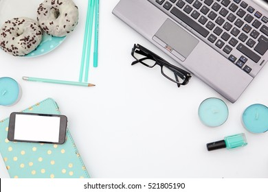 Flat lay, top view office table desk frame. Workspace with laptop, mint candle, mint diary, nail polish and mobile device and  donuts on white background.