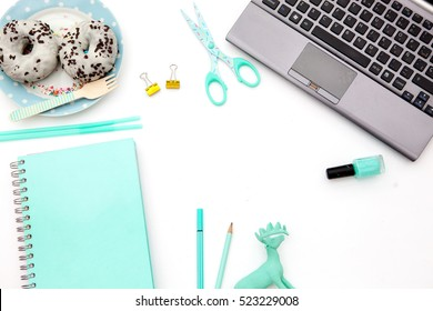 Flat lay, top view office table desk frame. Workspace with laptop, mint candle, mint diary, christmas items and mobile device and donuts on white background.