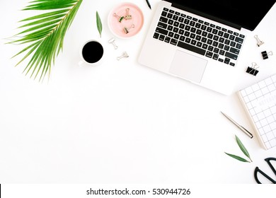 Flat lay, top view office table desk. Workspace with notebook, laptop, palm branch, coffee cup, scissors and clips on white background.