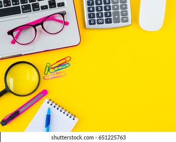 Flat lay, top view office table desk frame. feminine desk workspace with office accessories including calculator, glasses, clips, Magnifying glass, cutter, note book and blue pen on yellow background.