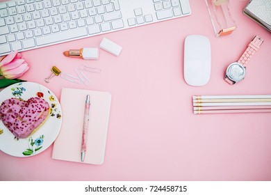 Flat lay, top view office table desk. feminine desk  pink  Flat lay, top view office table desk. feminine desk workspace with succulent, laptop, glasses, diary and golden clips on pink background.
