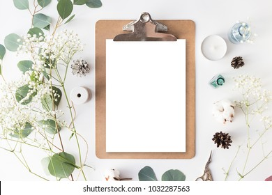 Flat lay top view photo of a clipboard on a white wooden background with gentle flowers and plants with a blank space for your design. Cute feminine mock up. Blank space.