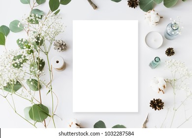Flat lay top view photo. Mockup on a white wooden background with gentle flowers and plants. Cute feminine image. Blank space.