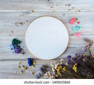 Flat lay top view photo of a mockup with an embroidery hoop and different  flowers. Feminine floral mock-up.