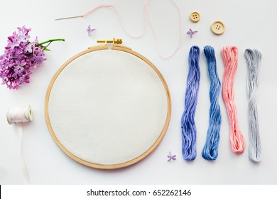 Flat lay top view photo of a mockup with an embroidery hoop and lilac flowers. Stylish feminine floral mock-up.