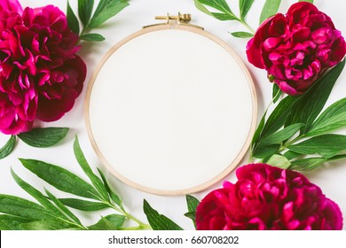 Flat lay top view photo of a mockup with embroidery hoop and peony flowers.