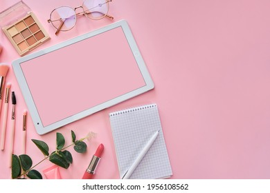 Flat lay, top view pink modern office table desk. Workspace with white tablet, notepad, glasses, pens, beauty accessories, keyboard, office supplies, green leaf, and coffee cup on pinkbackground