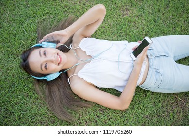 Flat lay or top view portrait of Smile beautiful Asian woman listen music  on grass in park. Happy brunette girl wear headphone and hold smartphone on hand.