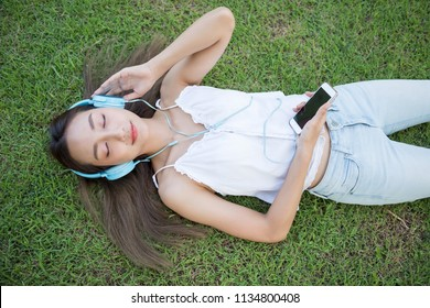 Flat lay or top view portrait of Smile beautiful Asian woman sleep and listen music on grass in park. Happy brunette girl wear headphone and hold smartphone on hand.