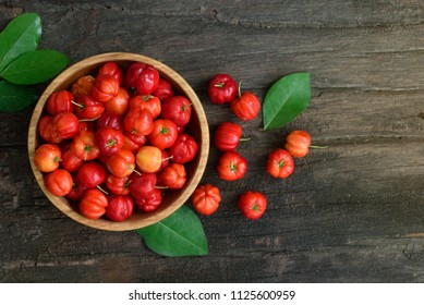 Flat lay (top view) Red Acerola Cherry in wooden bowl with green leaves on brown wood background, High vitamin C and anti oxidant fruits.