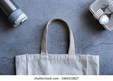 Flat lay or top view of reusable packaging consists of a beige cotton shopping bag, water tumbler, and plastic lunch box with stainless fork and spoon on the grey naked concrete with crack background