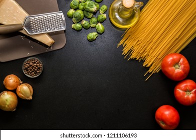 Flat lay, top view, space for text. Ingredients for italian pasta. Spaghetti, tomatoes, oil, onion, parmezan on black wooden background.