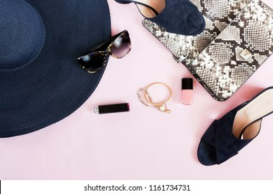 Flat lay, top view summer female fashion clothes background. stylish lyxury sandals, bag, sunglasses, make up products, accesories on pale pink background. copy space
