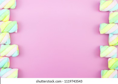Flat lay top view tasty appetizing concept, minimal Sweet Treat Swirl Candy Lollipop marshmallow Colourful pattern on pink pastel background and copy space