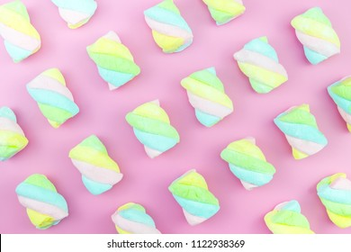 Flat lay top view tasty appetizing concept, minimal Sweet Treat Swirl Candy Lollipop marshmallow Colorful pattern on pink pastel background and copy space