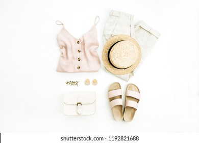 Flat lay, top view travel fashion boho style look with woman clothes and accessories. Straw hat, slippers, purse, blouse, bracelet, earrings, pants on white background.