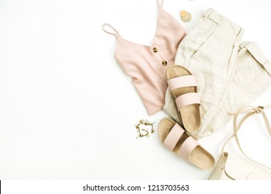 Flat lay, top view travel fashion boho style look with woman clothes and accessories. Slippers, purse, blouse, bracelet, earrings, pants on white background.