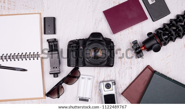Flat lay top view of traveler accessories on white wooden background. DSLR and action camera, paper notebook, passport, tripod, flash, laptop and smartphone