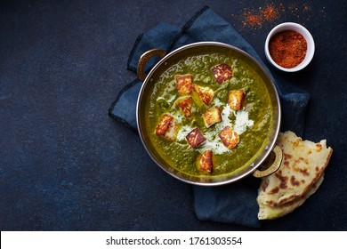 Flat lay top view of vegetarian palak paneer starter. Indian cuisine, curry dish with soft cheese and spinach on concrete background with copy space