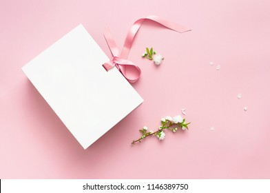 Flat lay top view White gift bag and spring flowers on a pink background. Greeting card with delicate flowers Pink floral background with copy space