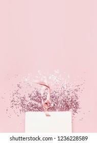 Flachbildschirm Draufsicht Weiße Geschenktasche und holografische Glitterkonfetti in Form von Sternen auf rosafarbenem Hintergrund. Grußkarte Feiertage Pastellfarben Hintergrund. Geburtstagsgratulation Weihnachten Neujahr