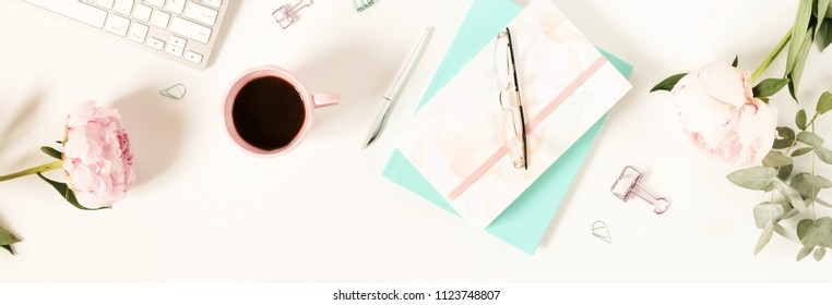 Flat lay top view women's office desk with flowers. Female workspace with laptop, peonies, accessories, notebook, glasses, cup of coffee on white background. Holiday background.Copy space banner