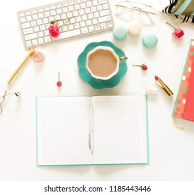 Flat lay, top view women's office desk with open notebook mock up. Female workspace with keyboard,  flowers roses,  accessories, , glasses, cup of coffee, cosmetics on white background.  .Copy space.