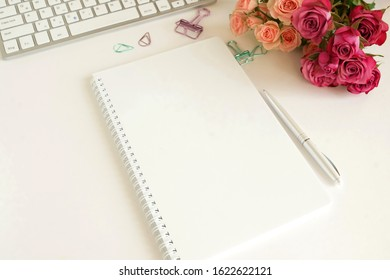 flat lay top view women's office desk on  white background selective focus. Female workspace with laptop, beautiful pink roses flowers in a vase, gift box, accessories, notebook mock up, glasses.