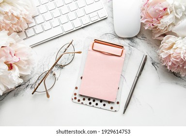 Flat lay top view women's office desk with flowers. Female workspace with laptop, flowers peonies, accessories, notebook, glasses, cup of coffee on white background. Holiday background.Copy space