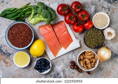 flat lay top-down composition of healthy food concept, salmon, tomatoes, berries, vegetables, seeds, nuts, olive oil.