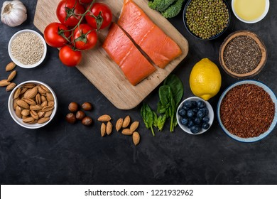 flat lay top-down composition of healthy food concept, salmon, tomatoes, berries, vegetables, chia seeds, nuts, olive oil.